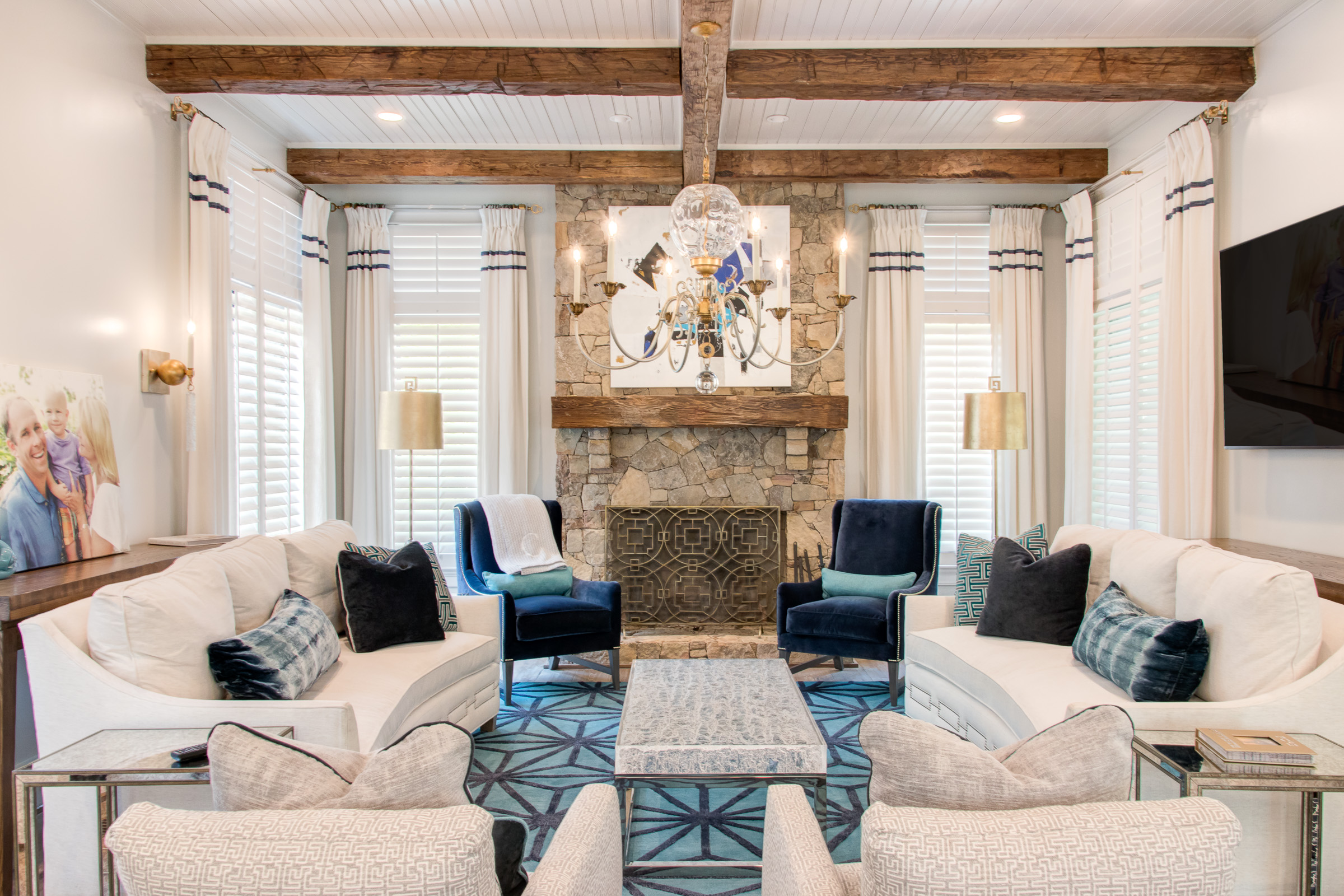 Exposed wood beams accent the stone fireplace and wood mantle surrounded by plush cream furniture.
