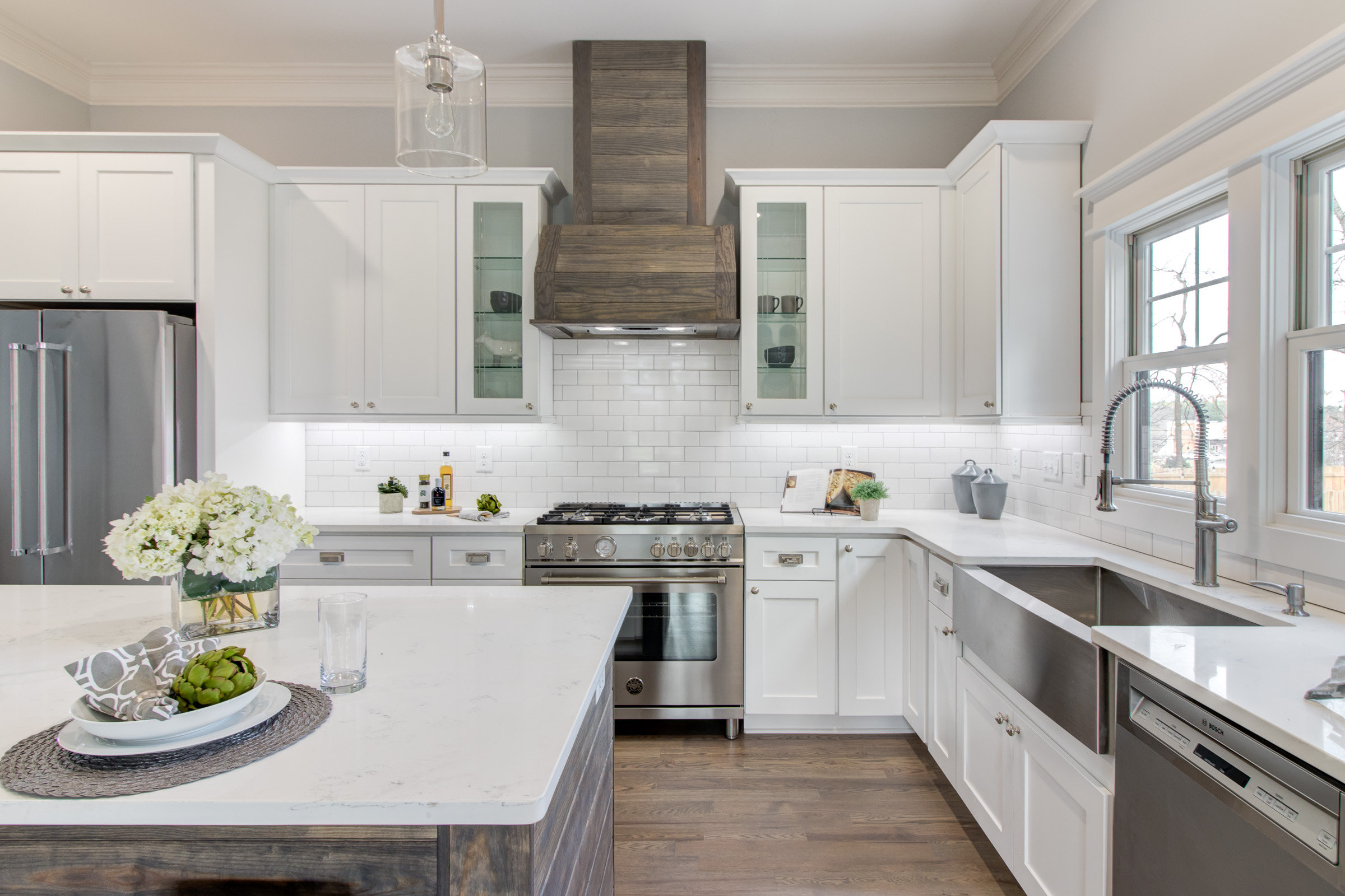 Bright and airy white kitchen with coordinating woof floors and range hood and a stainless steel farmhouse sink.