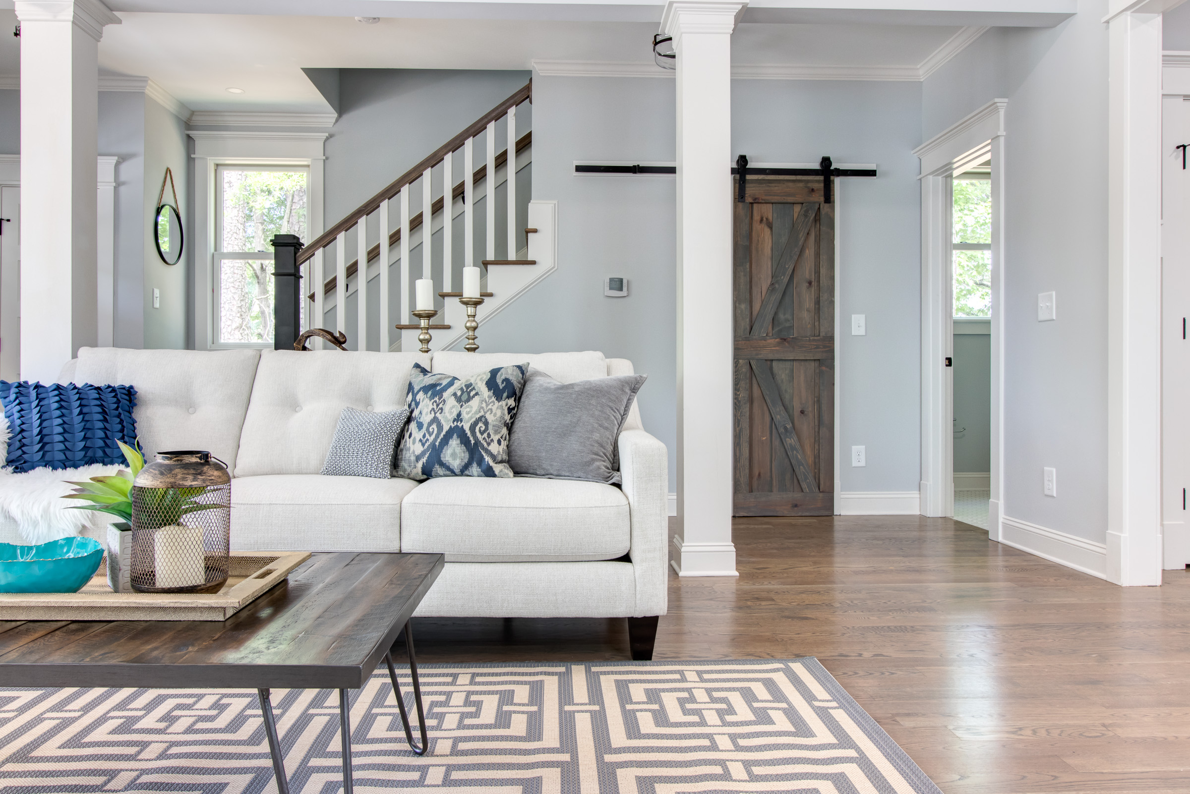 Grey and wood living room with a white couch and barn door closet.