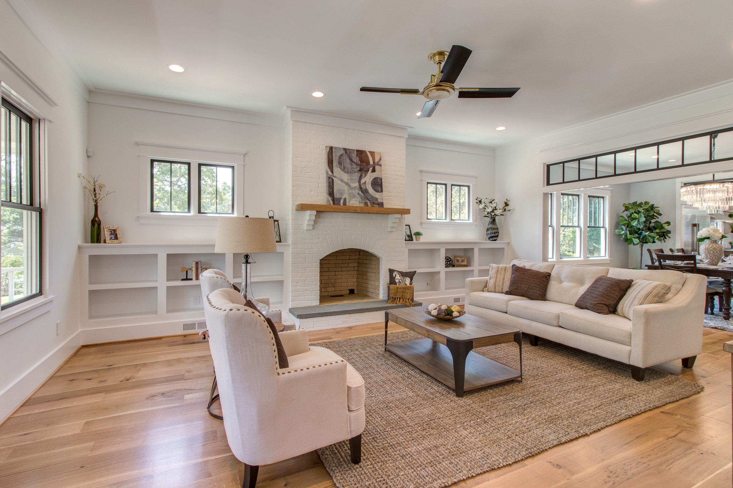 Spacious living room with cream walls, warm wood floors and black window trim.  Furnished with natural sisal rug and linen couches.