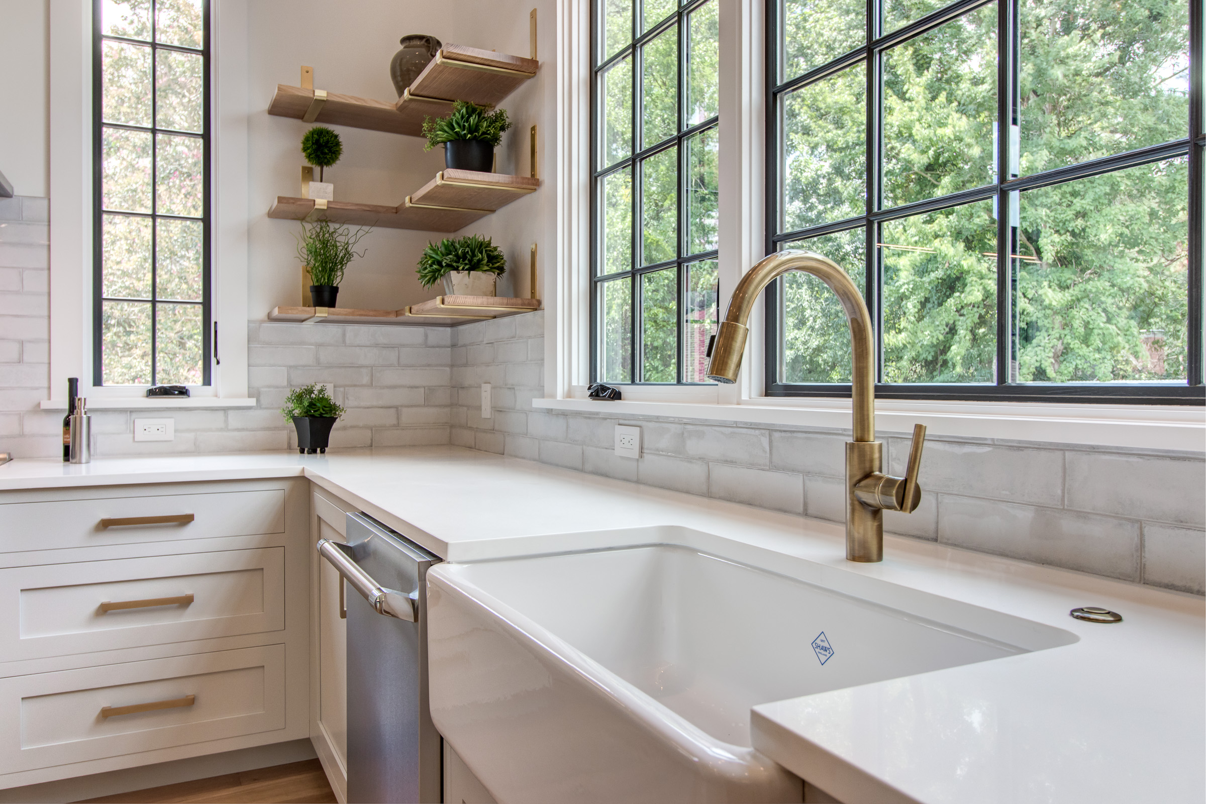 Farmhouse sink with antique brass faucet, open shelving, white counters, gold hardware.