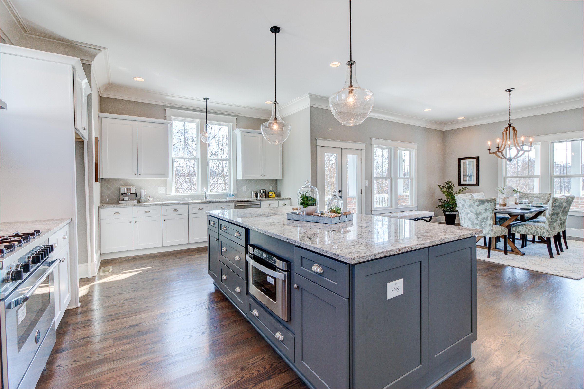 Large kitchen island in a dark bluie grey accents the white cabinetry and white counter tops. Wood flooring keeps the warm inviting feeling.