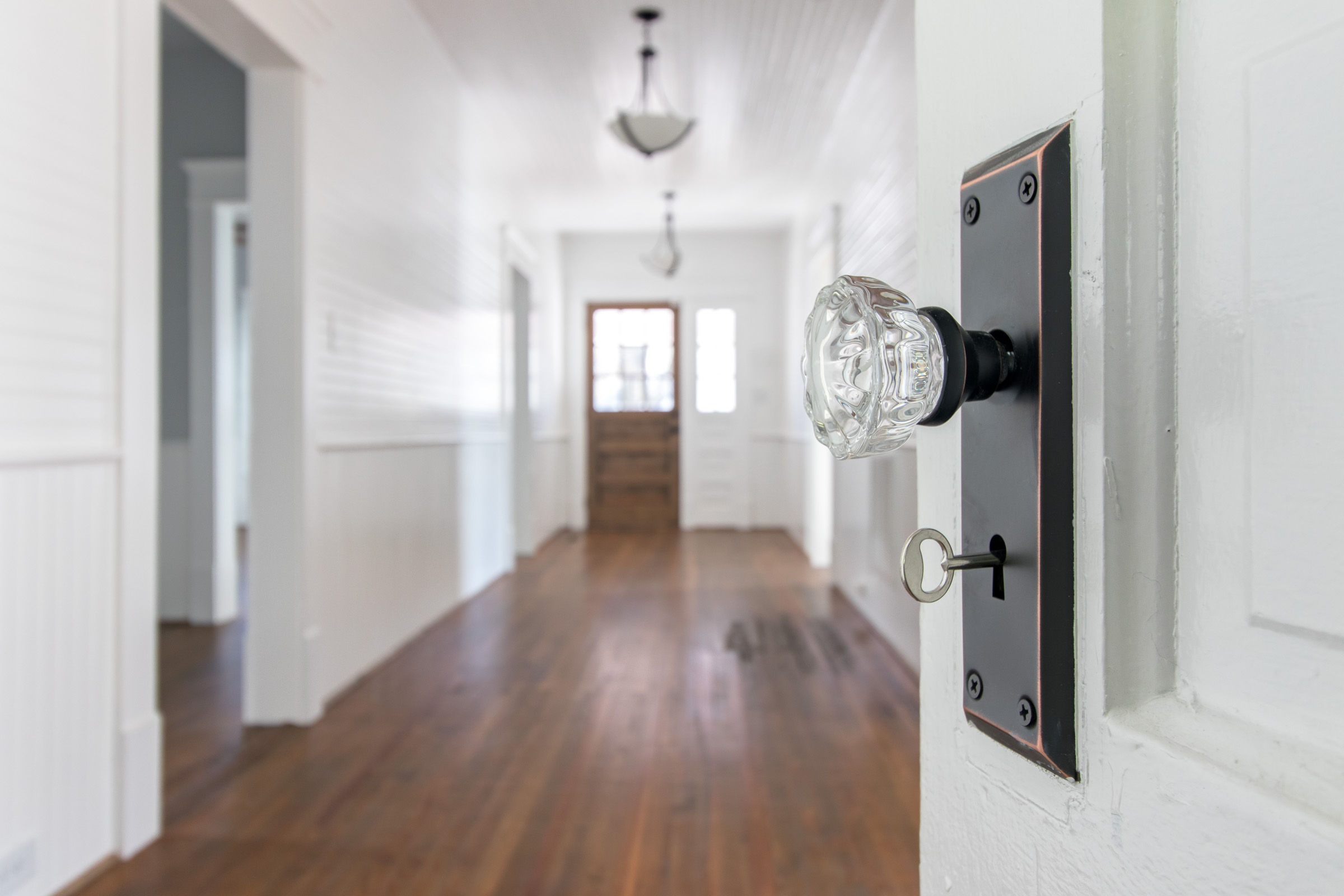 Restored home's spacious entry way with vintage details like this keyed glass door knob.